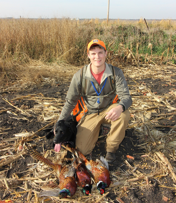 a young male hunter with 3 dead pheasants and black lab