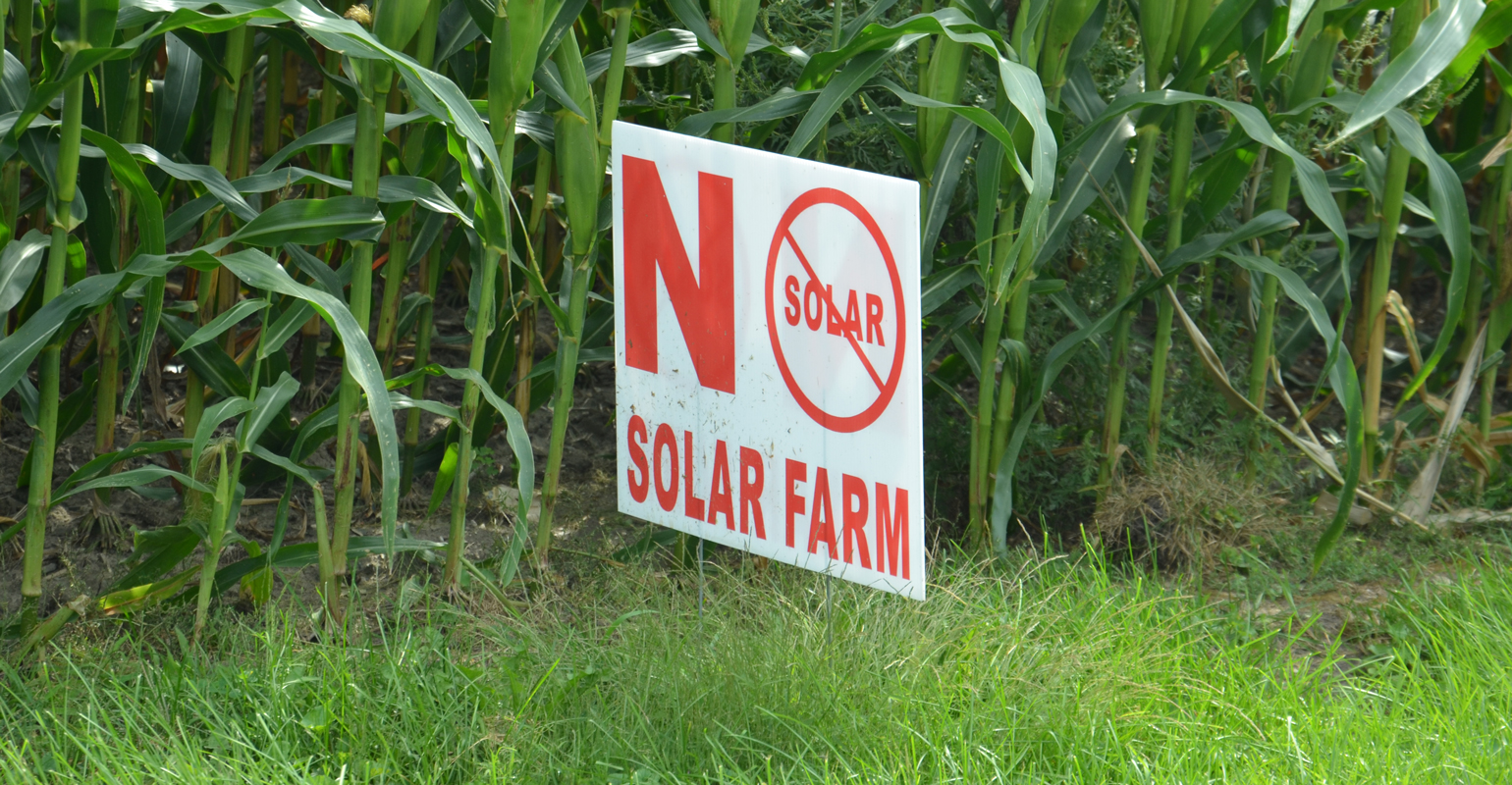 """no solar panels"" sign in field"