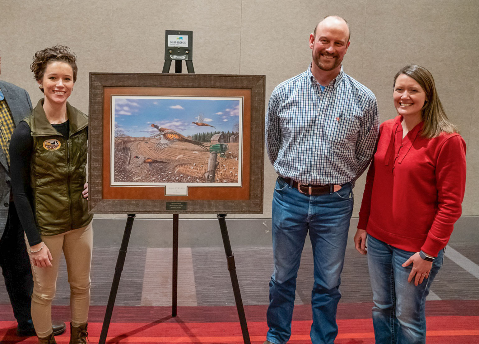 Melissa Shockman, Pheasants Forever precision agriculture and conservation specialist, Christof Just and his wife, Kelli pose after presentation of Farmer of the Year award