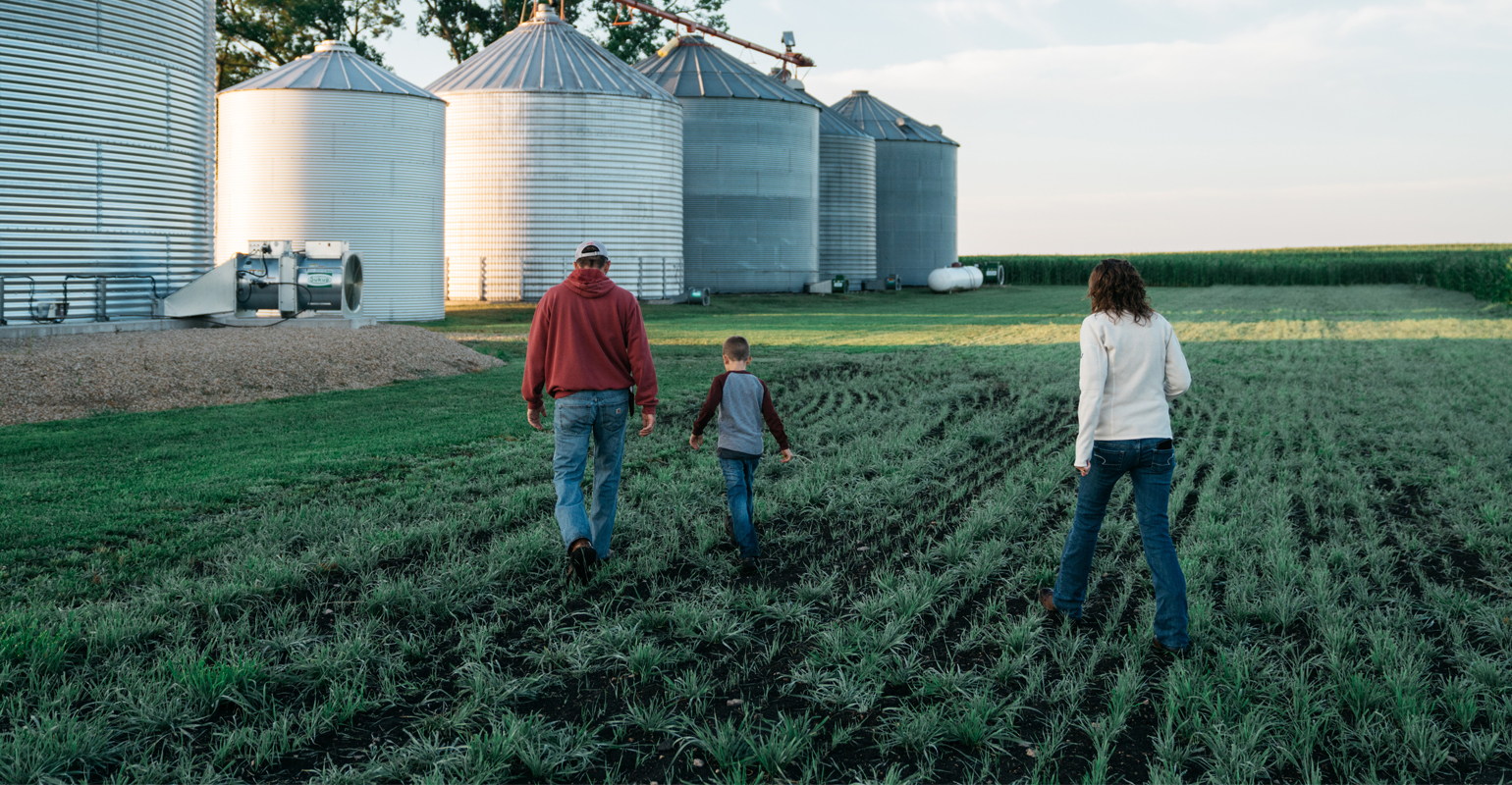 Matt and Nancy Bormann and child walking toward grain bins