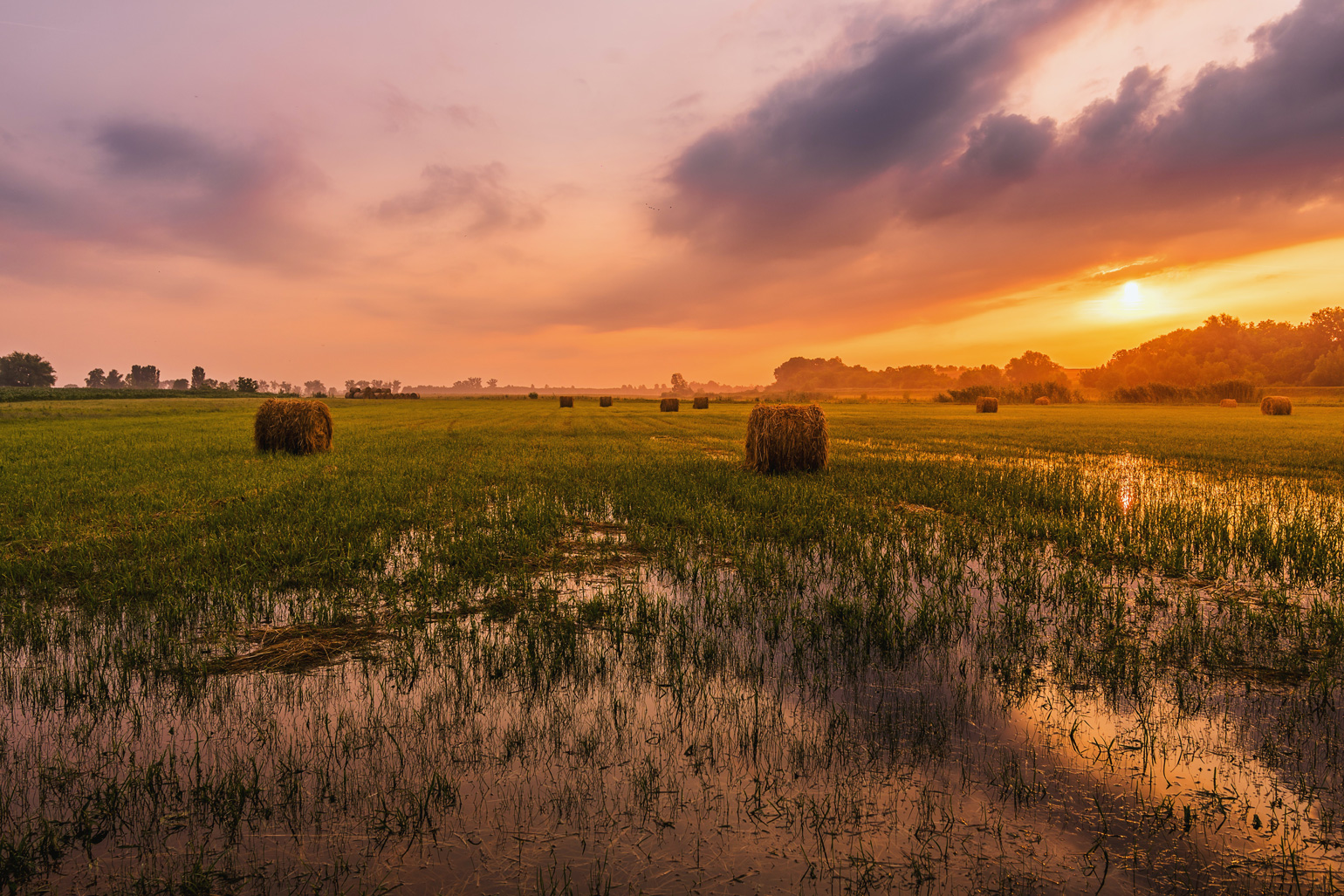 A wet field with hay bales pictured under a sun set