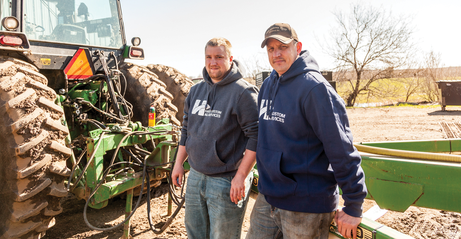 Two men standing between a John Deere rear tractor tire and implement.