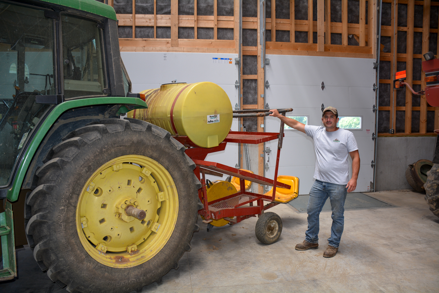 Harnish stands beside his water-wheel planter pulled by a John Deere 6410
