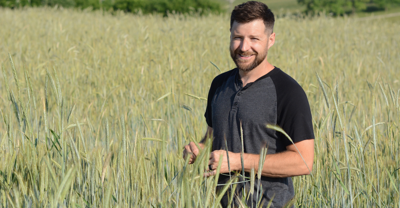 Jason Chatterton stands in field of cereal rye