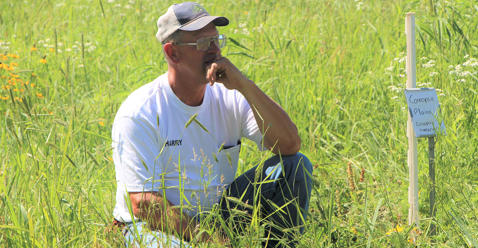 Montgomery County farmer Harry Cope kneels in native grass