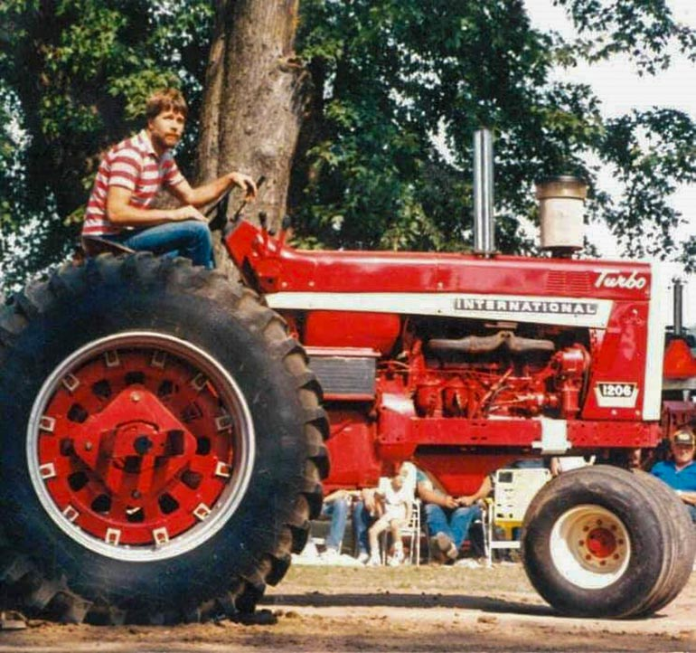 An old photograph of Doug Allen sitting on a red tractor
