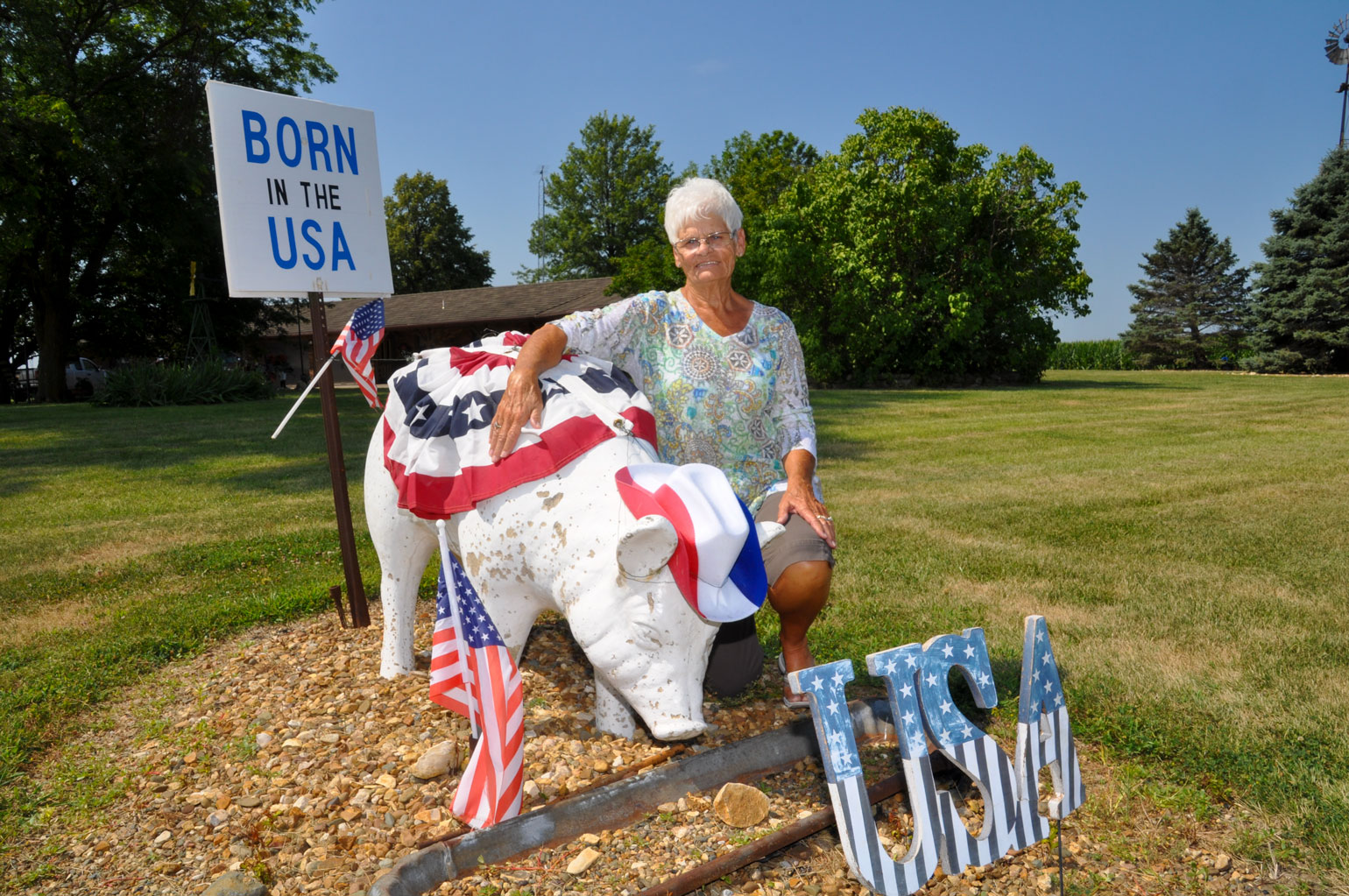 Sandy Nelson kneels beside s a concrete pig in her front yard decorated for the Fourth of July