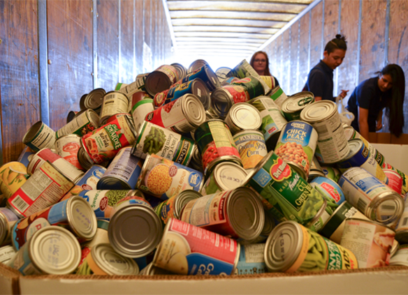 Boxes are filled to overflowing with cans donated by FFA members during the Heartland United Way Food 4 Families food drive at HHD.
