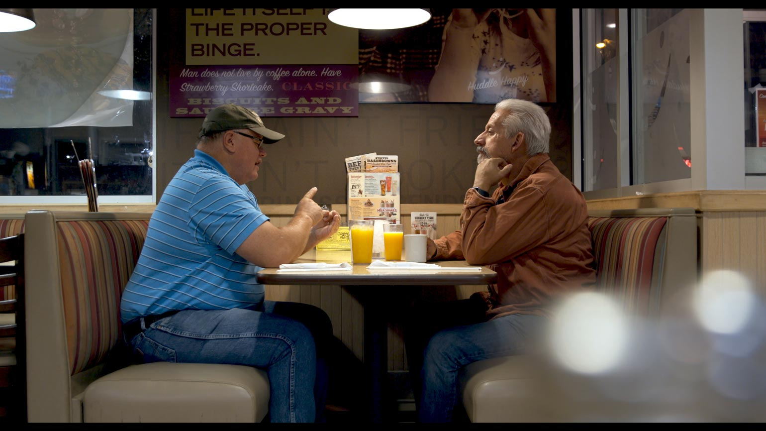 Two men sitting in a booth at a cafe while they have a conversation
