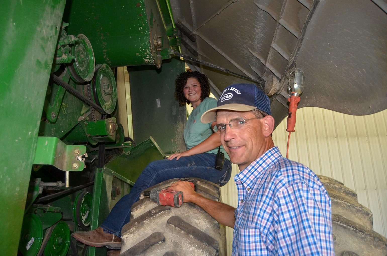 A young lady sitting on a tractor tire while she and her father work in the shop