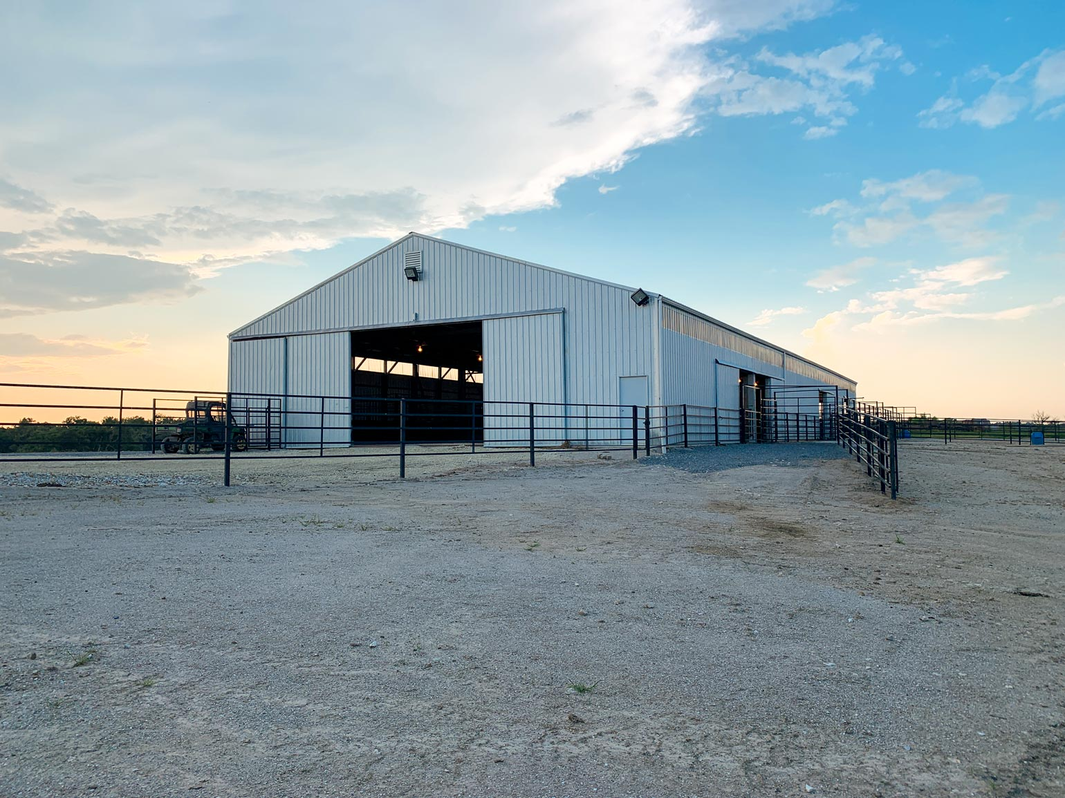 A white structure with metal fences surrounding it and used for cattle handling