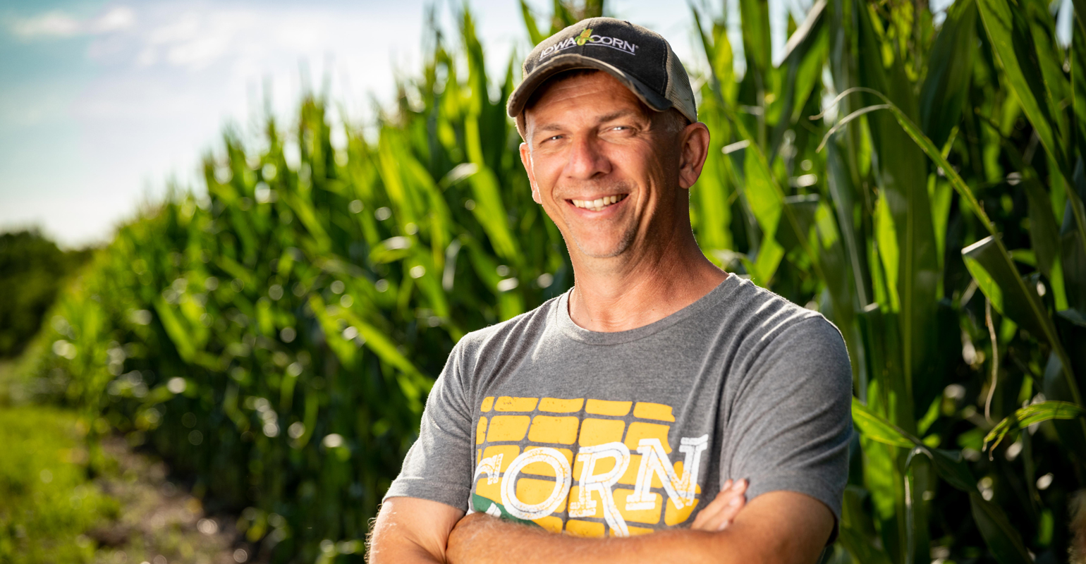 Man standing in front of corn field wearing T-shirt that says corn