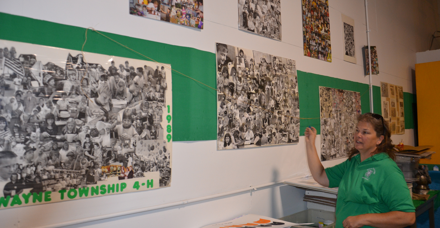 Alice Sweeney points to posters showing the history of Wayne Township 4-H