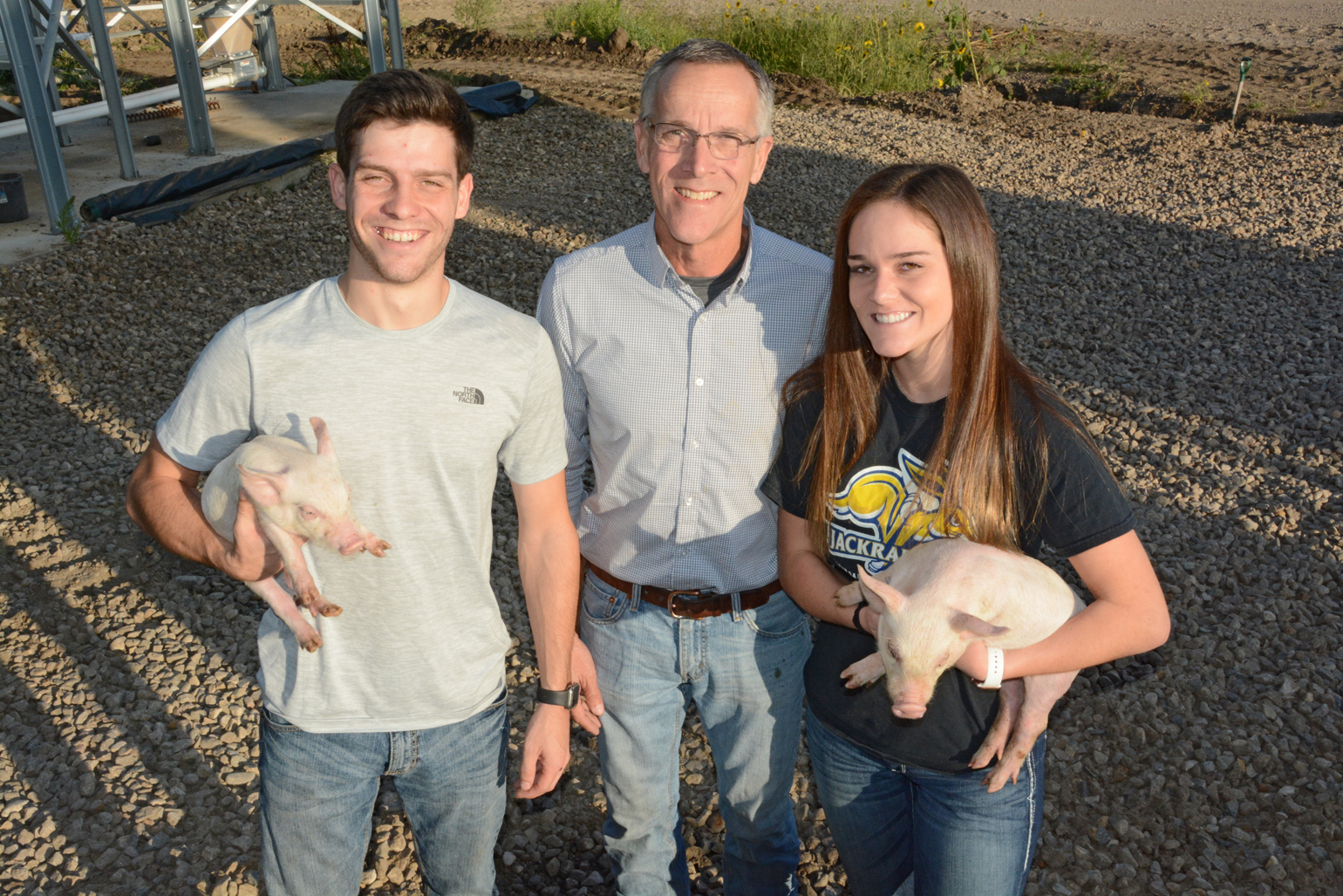 Karl Schenk and his children, Karl II and Kyra, holding piglets