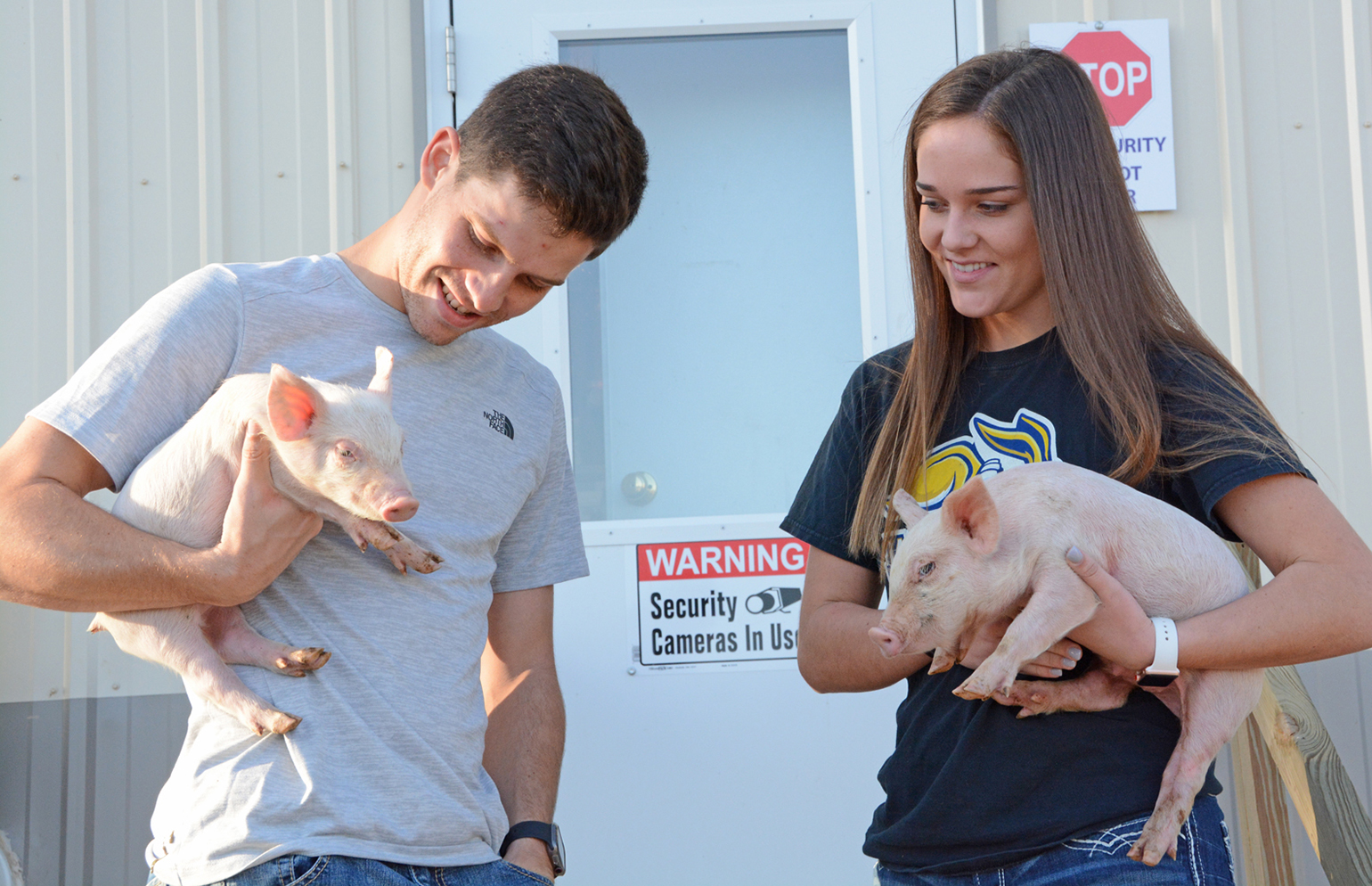 Karl II Schenk and his sister, Kyra, holds two of the healthy, antibiotic-free pigs