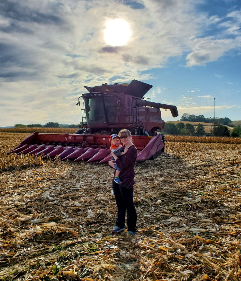 Sheilah Reskovac stands in a partly-harvested corn field holding her son with the combine behind them