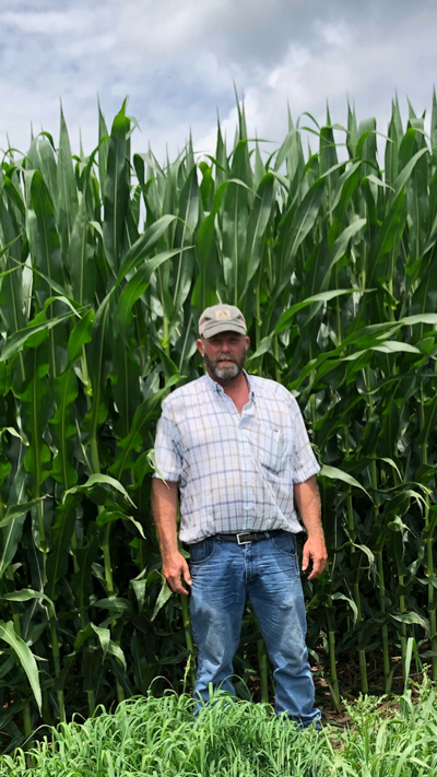 Drew Haines stands beside his record-yielding corn field