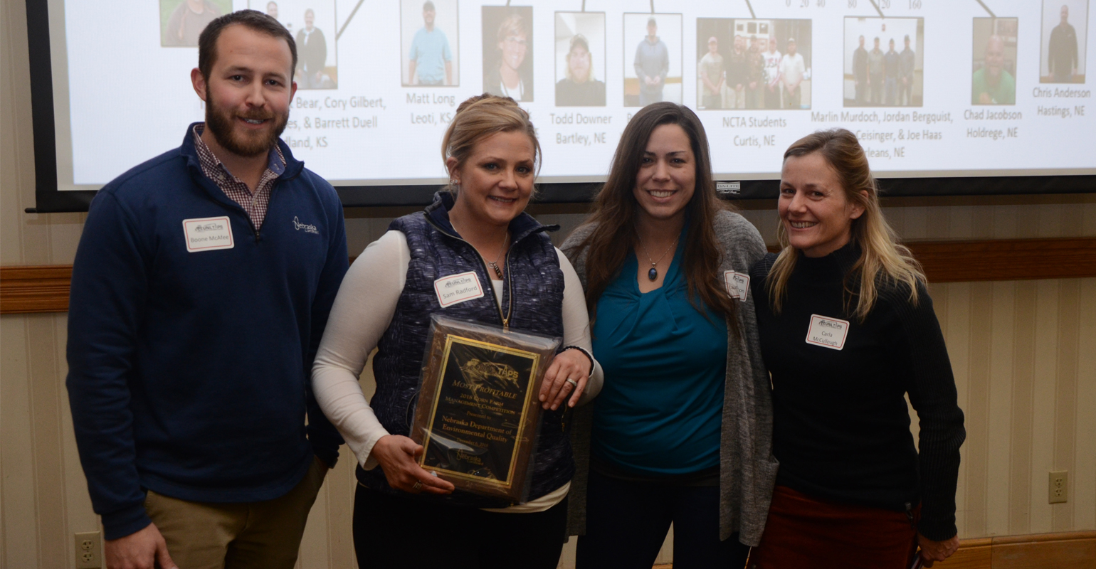 : Boone McAfee, director of research at the Nebraska Corn Board (one of the sponsors of the competition), hands the award for most profitable to the NDEQ team, including L-R: Sam Radford, Laura Johnson, and Carla McCullough