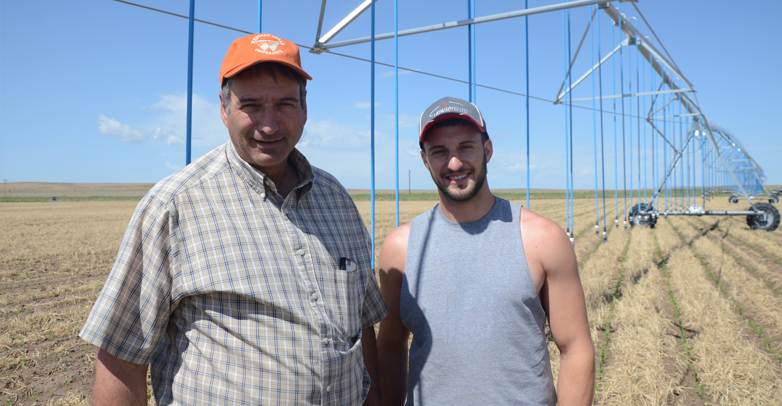 Nick (left) and Nicholas Lapaseotes stand next to the first center pivot they equipped with a LEPA system.