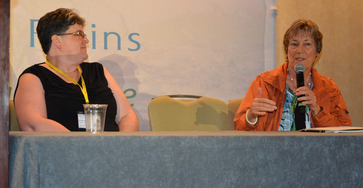 Soil health consultant Christine Nichols, left, listens to remarks from Christine Jones talk at the No-till on the Plains winter conference