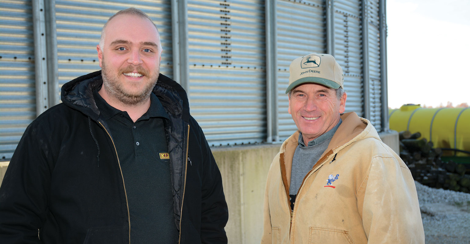 Two guys in front of a grain bin looking at the camera.