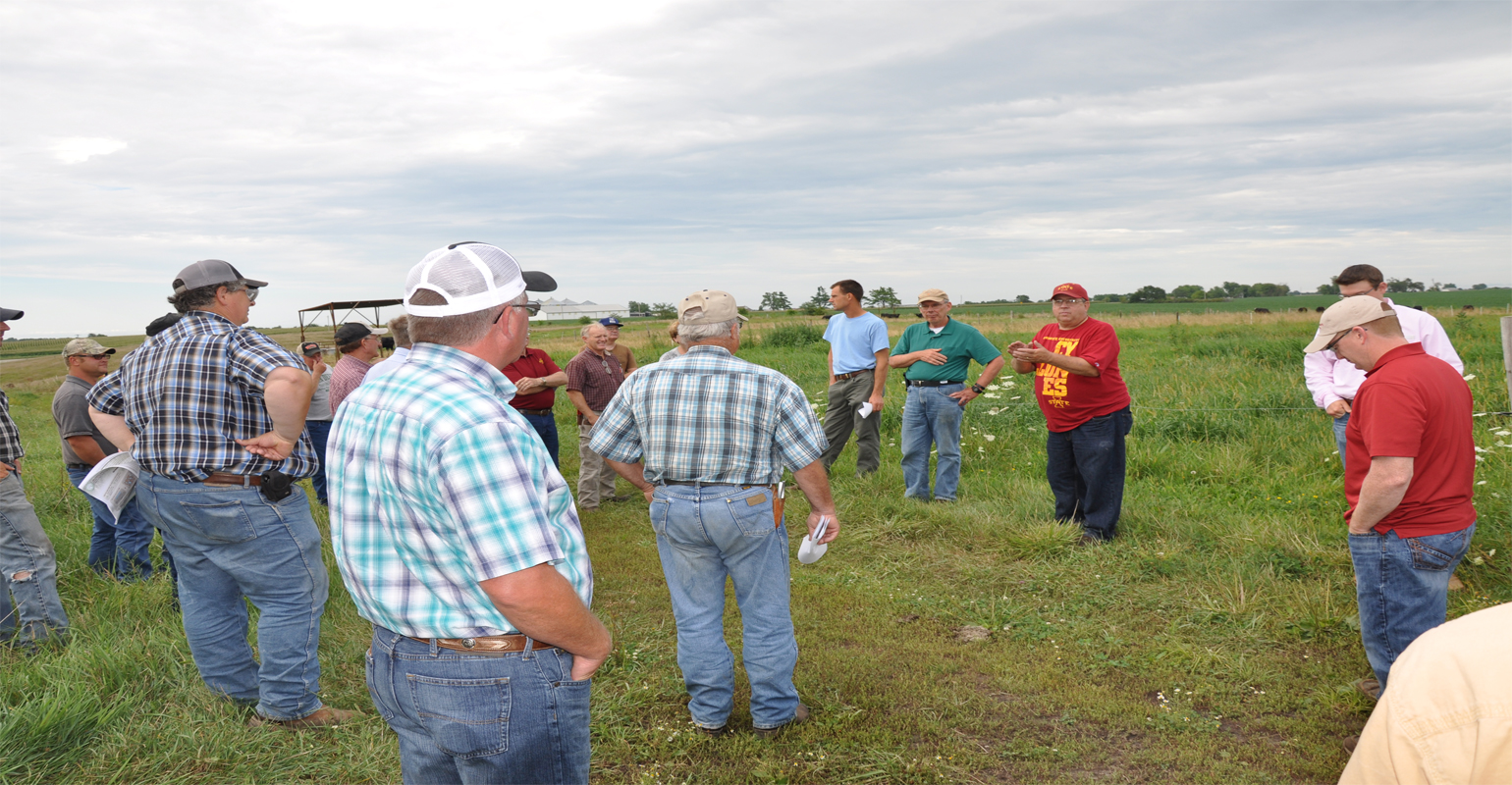 : Joe Sellers (red shirt and hat), discusses rotational grazing with Jim Russell, ISU professor emeritus of animal science (green shirt), at McNay Research Farm field day near Chariton.