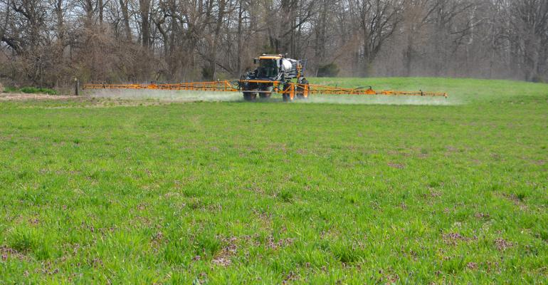 sprayer in field covered in cover crops