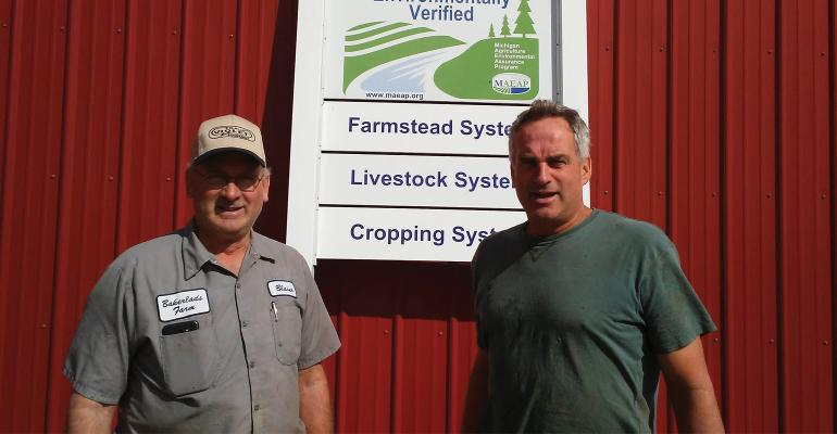 Blaine and Kim Baker of Bakerlads Farms stand infront of  a farmstead system livestock system and cropping system sign on a red building