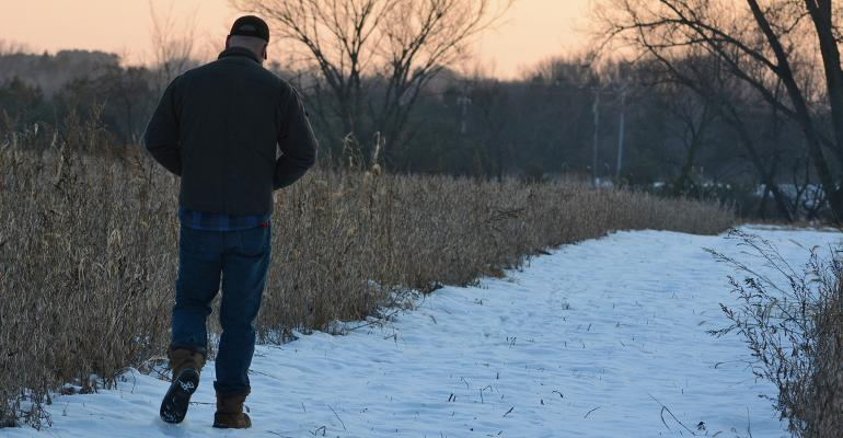 farmer walking on snowy path