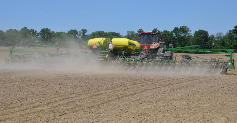 tractor and planter kicking up dust in field