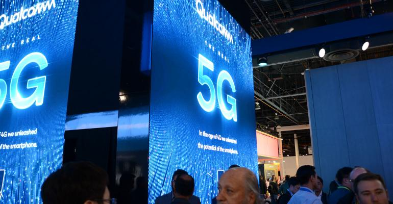 Trade show attendees walk near booth graphics advertising 5G internet