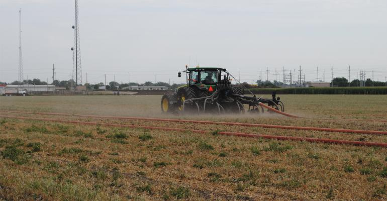 manure being applied by sprayer in field