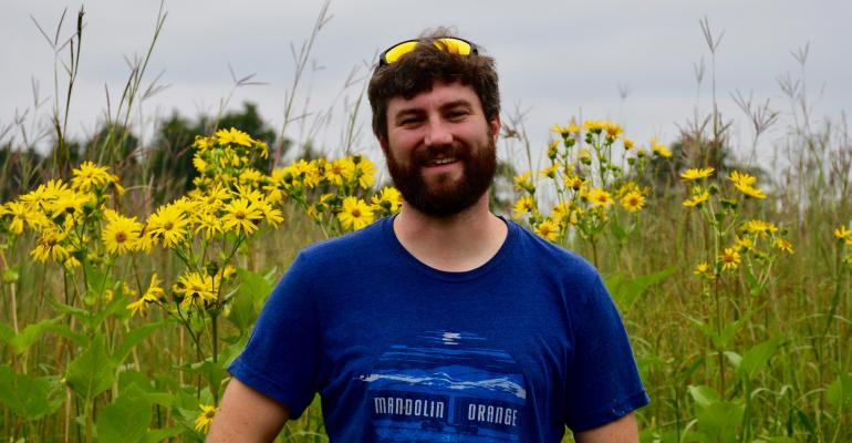 Sean Griffin stands in front of one of the research plots where he looking for native bees