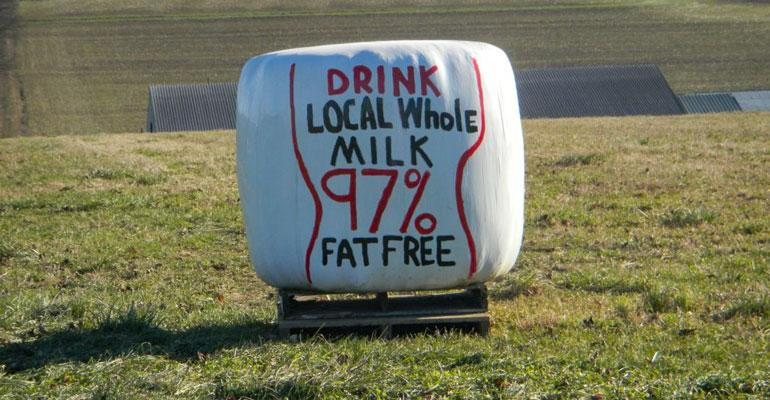 Plastic wrap on bale of hay in field reads 'Drink local whole milk 97% fat free'