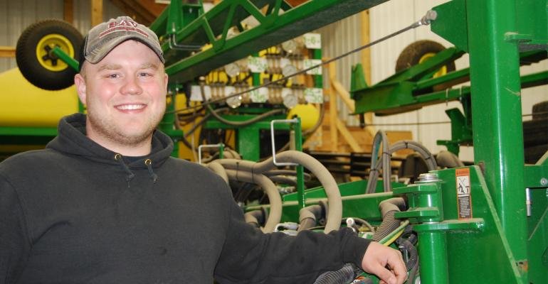 Brant Voss standing with farm equipment
