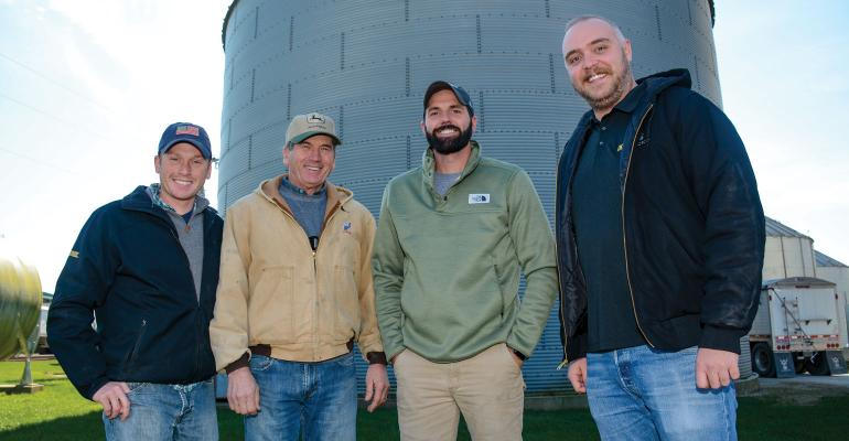 Four men standing in front of grain bin and looking at the camera