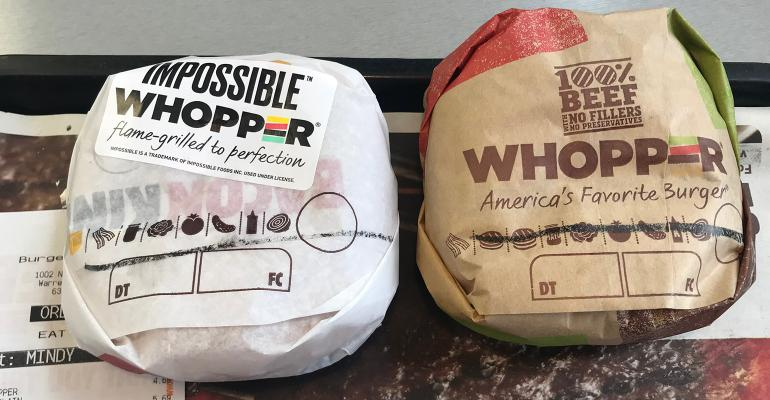 two wrapped burgers side-by-side