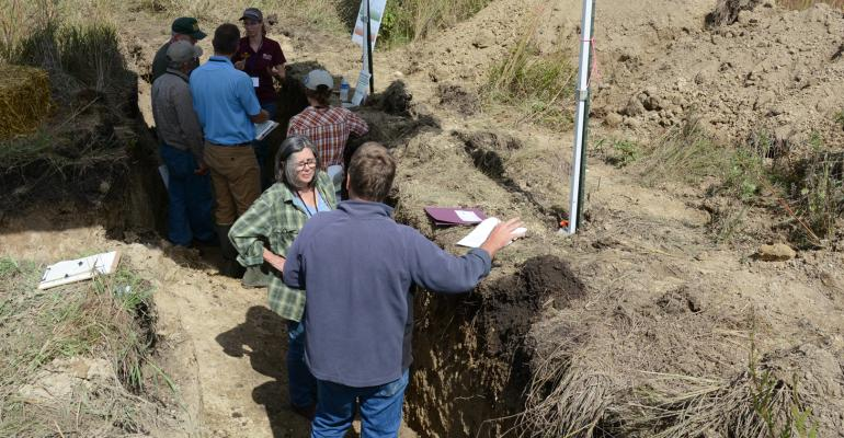 people standing in soil pits during a field day near Granite Falls, Minn., in Sept. 2019