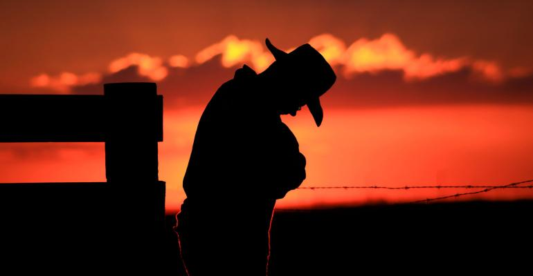 A farmer with his head down is silhouetted against a blazing orange sunset