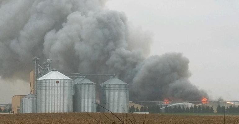 barn on fire with plumes of smoke