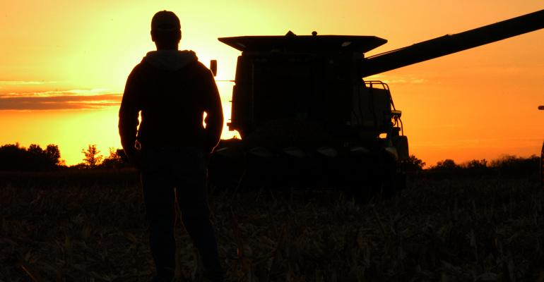 farmer looking into sunset with combine in background