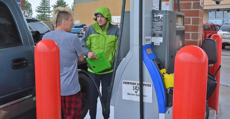 Chris Daniels talks about fuel options with customer at gas pump