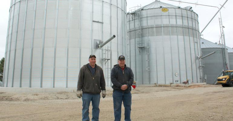Alex and Paul Schutjer in front of a 120,000-bushel dry storage bin