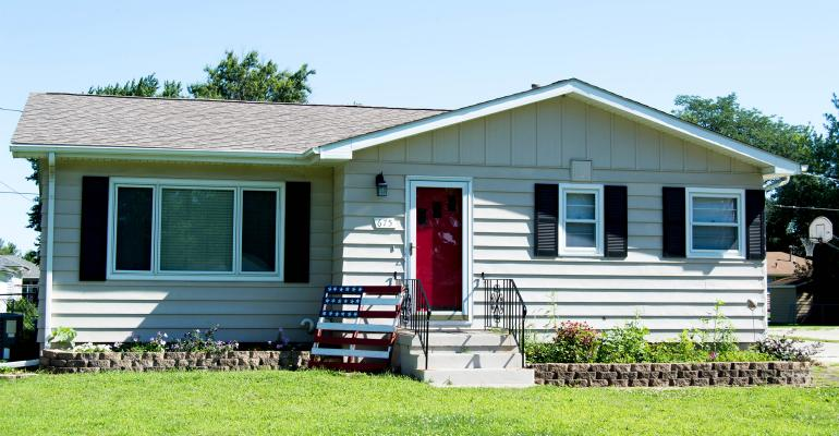 tan ranch house with red door and black shutters