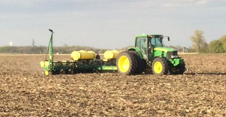 A farmer plants corn with a John Deere tractor