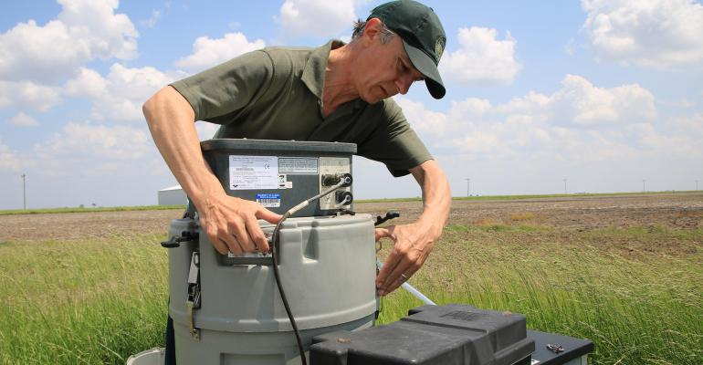 Lowell Gentry checks water gauges in field