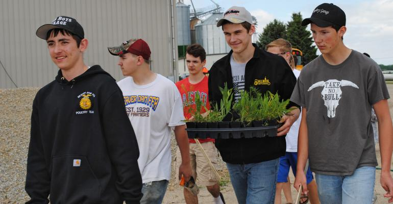students carry plants and tools