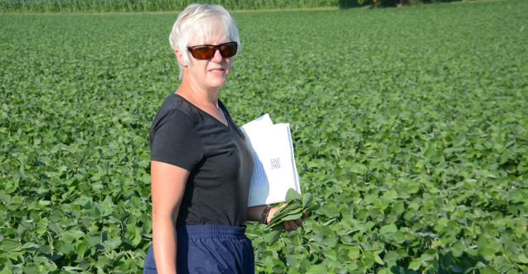 Betsy Bower standing in soybean field with clipboard