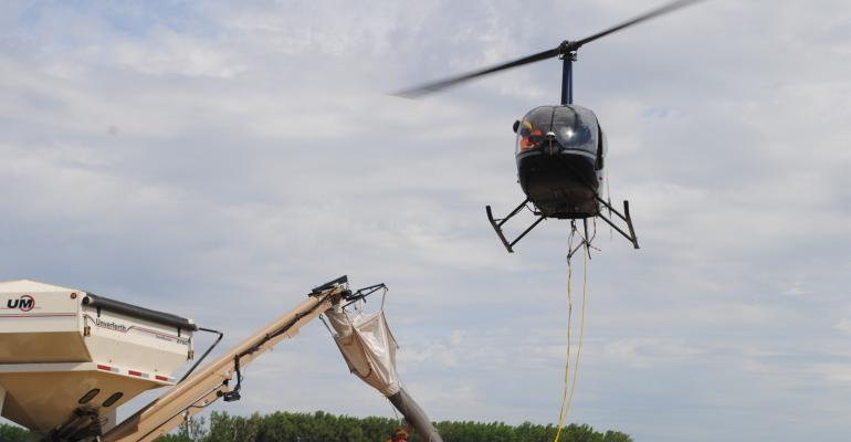 Brent Wulf, owner and operator of Hexagon Helicopters based in Bennington, Neb., hovers overhead while his ground crew, Taylor Schrunk, quickly fills the hopper of Wulf's patented aerial seeder