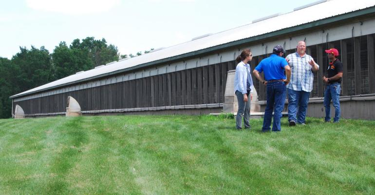 farmers talking outside of a barn
